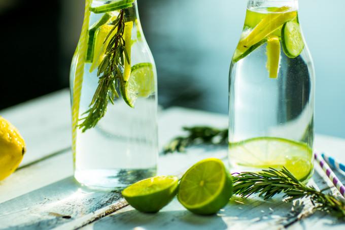 Garrafas com água DETOX de limão, além de outros ingredientes na mesa.