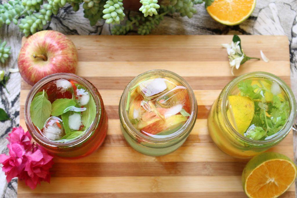 Recipientes vistos de cima com água DETOX, com ingredientes dentro dos copos e alguns na tábua.