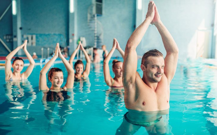 Pessoas de diversas idades praticando exercícios físicos - hidroginástica - durante o verão